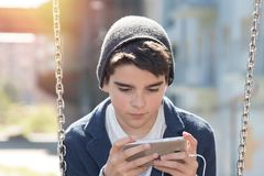 Child with the cellphone. In park swings stock image