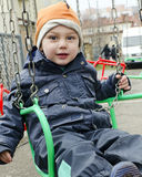 Child on chain swing. On merry-go-round at funfair Royalty Free Stock Image