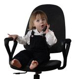 Child in the chair. Child sitting in the office chair and talking mobile phone Stock Photo