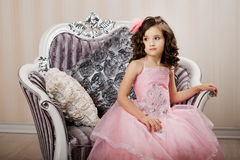 Child on a chair in a nice dress Stock Photography