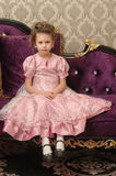 Child on a chair in a nice dress Stock Photos