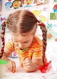 Child with chalk draw in playroom. Child with piece of chalk draw in playroom. Preschool stock photography