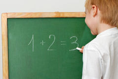 The child with a chalk near a board Stock Photography
