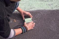 Child with chalks on a asphalt street Royalty Free Stock Photos