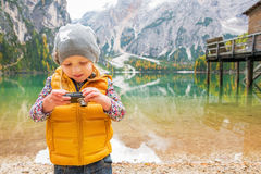 Child checking photos in camera on lake braies Royalty Free Stock Images