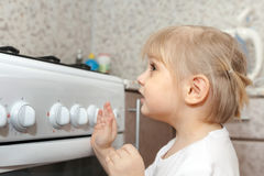 Child checking   stove at domestic kitchen Royalty Free Stock Images