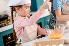 child in chef hat and apron whisking eggs stock image