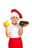 Child chef hold eggplant and pepper Stock Images