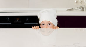 Child in a chefs toque hiding behind a counter Stock Photography