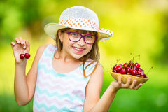 Child with cherries. Little girl with fresh cherries. Young cute caucasian blond girl wearing teeth braces and glasses. Royalty Free Stock Images