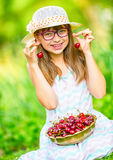 Child with cherries. Little girl with fresh cherries. Young cute caucasian blond girl wearing teeth braces and glasses. Stock Photography