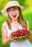 Child with cherries. Little girl with fresh cherries. Young cute caucasian blond girl wearing teeth braces and glasses. Royalty Free Stock Photography