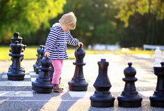 Child with chess figures outdoor Stock Photo