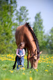 Child with chestnut horse in field. Small girl with chestnut horse in the meadow at spring Stock Image