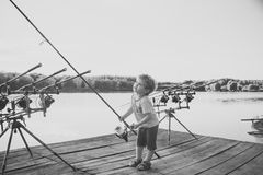 Child Childhood Children Happiness Concept. Angling child with fishing rod on wooden pier. Angling, fishing, activity, adventure, hobby, sport Royalty Free Stock Images