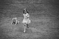 Child Childhood Children Happiness Concept. Kids run and fall on green grass on summer day. On natural landscape. Chase, race, catch, competition concept Stock Photo