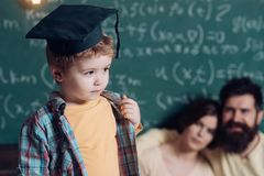 Child and childhood. Little child in graduation cap. Child in classroom. A child can ask questions that a wise man. Child and childhood. Little child in stock photo