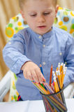 Child choose between colored pencil Stock Photos