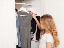Girl chooses clothes from the closet. Child. Child chooses clothes from the closet. Happy girl stock photography