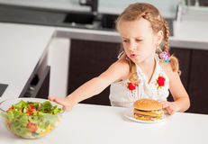 Child chooses between a healthy and unhealthy food Stock Images