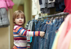 Child chooses jeans at  shop Royalty Free Stock Image