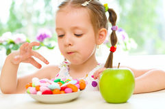 Child choosing between apple and sweets Stock Images