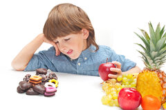 Child choosing food. Child boy choosing between healthy food and chocolate sweets royalty free stock image