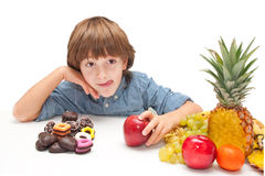 Child choosing food. Child boy choosing between healthy food and chocolate sweets royalty free stock images