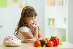 Child choosing between healthy vegetables and Stock Photos