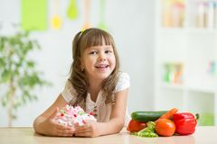 Child choosing sweet cake instead of healthy Stock Photography