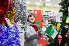 Child choosing toys for Christmas tree in store. stock images