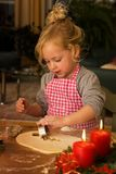 A child at Christmas in Advent when baking cookies Royalty Free Stock Photos