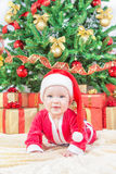 Child in christmas hat against decorated fir tree Royalty Free Stock Photo