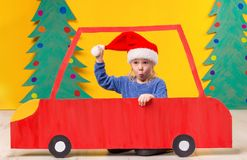 Child with Christmas hat driving a car made of cardboard. Christmas concept. New Year`s holidays. Child with Christmas hat driving a car made of cardboard Stock Photography