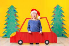 Child with Christmas hat driving a car made of cardboard. Christmas concept. New Year`s holidays. Royalty Free Stock Photos