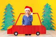 Child with Christmas hat driving a car made of cardboard. Christmas concept. New Year`s holidays. Royalty Free Stock Photo