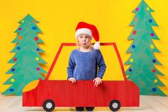 Child with Christmas hat driving a car made of cardboard. Christmas concept. New Year`s holidays. Royalty Free Stock Photography