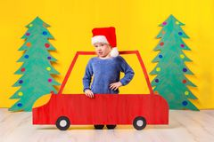 Child with Christmas hat driving a car made of cardboard. Christmas concept. New Year`s holidays. Stock Photos