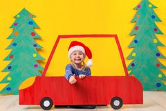 Child with Christmas hat driving a car made of cardboard. Christmas concept. New Year`s holidays. Stock Photo