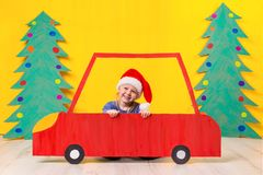Child with Christmas hat driving a car made of cardboard. Christmas concept. New Year`s holidays. Stock Photography