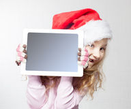 Child in christmas hat with tablet Stock Photo