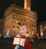 Child with Christmas present box near Palazzo Vecchio, Florence Stock Photos