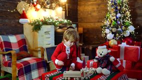 Child with a Christmas present on wooden house background. Cheerful cute child opening a Christmas present. Merry stock video footage