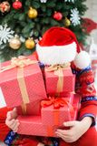 Child in christmas red hat hiding behind pile of holiday present Royalty Free Stock Photography