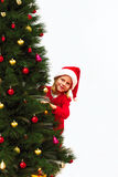 Child in a christmas red hat peeking out from behind the Chris Royalty Free Stock Images