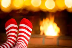 Child in Christmas socks near fireplace Stock Photo