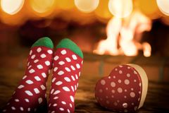 Child in Christmas socks near fireplace Stock Photography