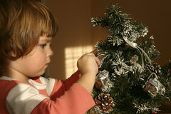 Child and Christmas tree. Little child decorating Christmas tree Royalty Free Stock Images