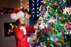 Child at Christmas tree and fireplace on Xmas eve. Family with kids celebrating Christmas at home. Little girl decorating xmas tree and opening presents. Gifts Stock Image