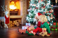 Child at Christmas tree. Kids at fireplace on Xmas. Children at Christmas tree and fireplace on Xmas eve. Family with kids celebrating Christmas at home. Boy and Stock Photo